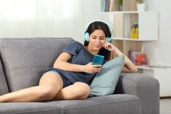 Relaxed teen listening to music lying on a couch. In the living room at home Royalty Free Stock Photo