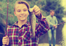 Relaxed teenage boy holding catch freshwater fish. In hands on vacation Royalty Free Stock Photo