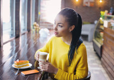 Relaxed teenage girl enjoying her coffee break Royalty Free Stock Images