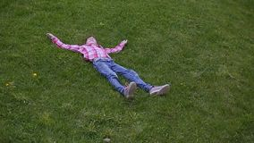 Relaxed teenage girl lying in grass. Lifestyle, summer vacation and people concept.