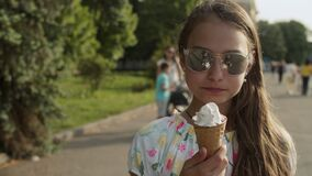 Relaxed teenage girl walking in amusement park. Cute girl eating ice cream