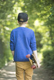 Relaxed Teenage skateboard boy outdoor. Blond teenage boy walking relaxed with skateboard under arm along alley with trees and bushes as blurred background Stock Images