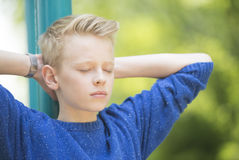 Relaxed teenager boy with closed eyes outdoor. Portrait serious and confident looking blond teenage boy outdoor with closed eyes, relaxed and positive with arms Royalty Free Stock Images