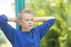 Relaxed teenager boy portrait outdoor. Portrait serious and confident looking blond teenage boy outdoor, relaxed and positive with arms up behind head, blurred Stock Photos