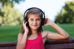 Relaxed Teenager girl listening music in park Stock Photo