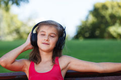 Relaxed Teenager girl listening music in park Stock Images
