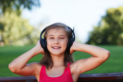 Relaxed Teenager girl listening music in park Royalty Free Stock Image