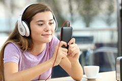 Relaxed teenager listening to music in an hotel bar. Relaxed teenager wearing headphones is listening to music holding a smart phone in an hotel bar royalty free stock photos