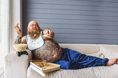 Relaxed thick guy entertaining with pizza and television Royalty Free Stock Photography