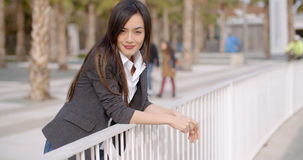 Relaxed thoughtful young woman leaning on railings Stock Image