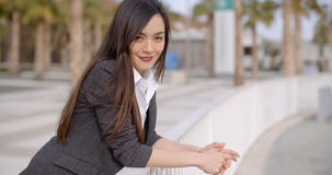 Relaxed thoughtful young woman leaning on railings Stock Photos