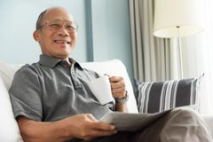 Relaxed time, Free time, Smiling, Retirement. Happy Asian senior man smiling and drinking hot coffee while reading newspaper at his house. Relaxed, Free time stock images