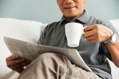 Relaxed time, Free time, Smiling, Retirement. Happy Asian senior man smiling and drinking hot coffee while reading newspaper at his house. Relaxed, Free time stock photo