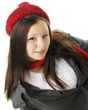 Relaxed Tween. An attractive preteen reclined in her jacket and red winter hat and scarf.  On a white background Royalty Free Stock Image