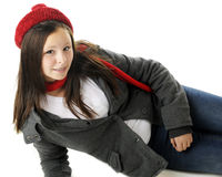 Relaxed Tween. An attractive preteen reclined in her jacket and red winter hat and scarf.  On a white background Stock Photos