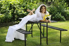 Relaxed before the Wedding. A beautiful young bride happily sprawled across a picnic table, barefoot in her wedding gown royalty free stock photography