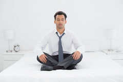 Relaxed well dressed man sitting with eyes closed on bed Stock Photography