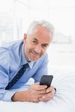 Relaxed well dressed man text messaging in bed Royalty Free Stock Images
