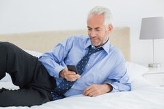 Relaxed well dressed man text messaging in bed Royalty Free Stock Photo