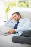 Relaxed well dressed man watching tv in living room Royalty Free Stock Images