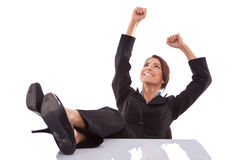Relaxed and winning business woman sitting. With her legs on desk and hands in the air Stock Photos