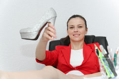 Relaxed and winning business woman sitting with her legs on desk Royalty Free Stock Images