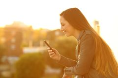 Relaxed woman in a balcony checking smart phone. Side view portrait of a relaxed woman in a balcony checking smart phone content at sunset stock photo