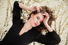 Relaxed woman in black dress lying on sparkling background Stock Photography