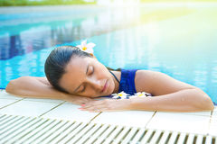 Relaxed woman in blue dress in the pool, eyes closed Royalty Free Stock Photos