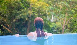 Relaxed woman in blue swimming pool. Girl in open swimming pool. Summer vacation vintage toned photo. Tropical jungle hotel scene. Exotic holiday. Outdoor Stock Images
