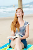 Relaxed Woman With Book On Beach Stock Image