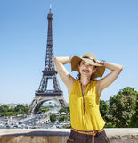 Relaxed woman in bright blouse in front of Eiffel tower in Paris. Having fun time near the world famous landmark in Paris. Portrait of relaxed young woman in Royalty Free Stock Images