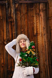 Relaxed woman with Christmas tree in front of rustic wood wall Royalty Free Stock Photos