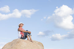 Relaxed woman with closed eyes on top of rock Royalty Free Stock Photos