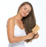 Relaxed woman combing hair Stock Photos