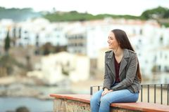 Relaxed woman contemlating views in a coast town. Relaxed woman contemlating views sitting on a ledge in a coast town on vacation royalty free stock images
