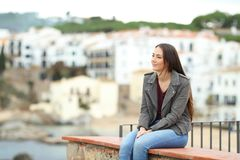 Relaxed woman contemplating views in a coast town. Relaxed woman contemplating views sitting on a ledge in a coast town on vacation royalty free stock images