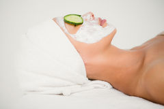 Relaxed woman with cucumber on a creamed face Royalty Free Stock Images
