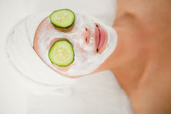 Relaxed woman with cucumber on a creamed face Stock Photos
