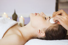 Relaxed woman with a deep cleansing nourishing face mask applied. To her face. Spa treatment Stock Images