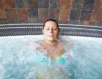A relaxed woman doing hydromassage in a beauty spa Stock Photography