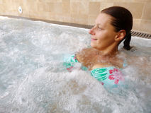 A relaxed woman doing hydromassage in a beauty spa Royalty Free Stock Image