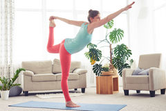 Relaxed woman doing yoga on yoga mat in living room Stock Image