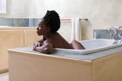 Relaxed woman dreaming in bath tub. Beautiful woman with afro hair dreaming in bath tub stock photography