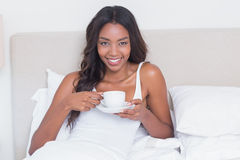 Relaxed woman drinking coffee in bed Stock Photography
