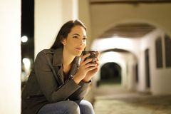 Relaxed woman drinking coffee in the night stock photography