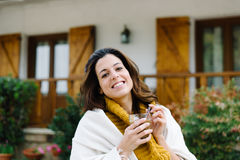 Relaxed woman drinking coffee outside home on autumn Royalty Free Stock Photo