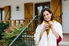Relaxed woman drinking coffee outside home on autumn Stock Photos