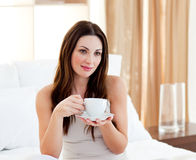 Relaxed woman drinking coffee sitting on bed Royalty Free Stock Photography