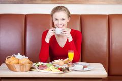 Relaxed woman drinking cup of coffee at breakfast table Stock Photography